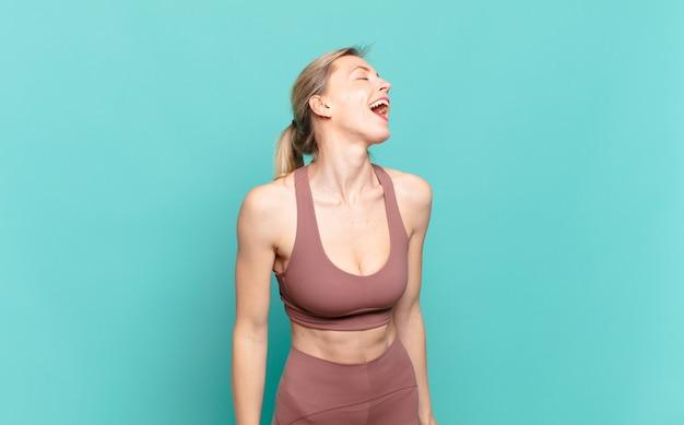 若いブロンドの女性は猛烈に叫び、積極的に叫び、ストレスと怒りを見ていた。スポーツコンセプト