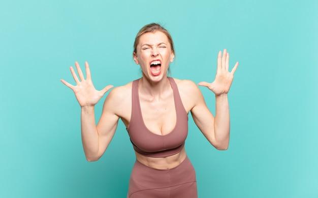 Молодая блондинка кричит от паники или гнева, потрясена, напугана или разъярена, положив руки на голову. спортивная концепция