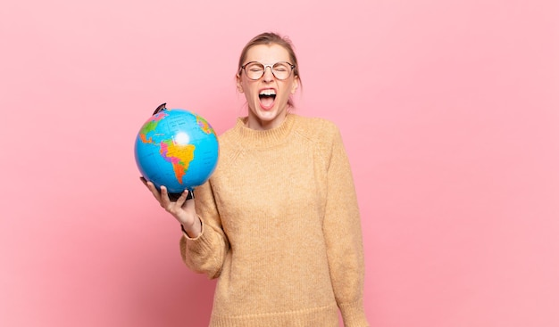 Молодая блондинка агрессивно кричит, выглядит очень рассерженной, расстроенной, возмущенной или раздраженной, кричит «нет». мировая концепция