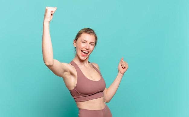 意気揚々と叫び、興奮し、幸せで驚きの勝者のように見え、祝う若いブロンドの女性。スポーツコンセプト