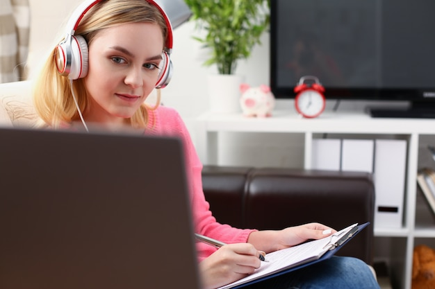 Young blond woman sit on the sofa in livingroom hold binder in arms work with laptop listen to music