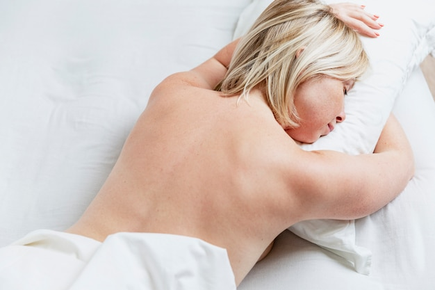 Young blond woman sleeping on her stomach in bed. full sleep and relaxation.