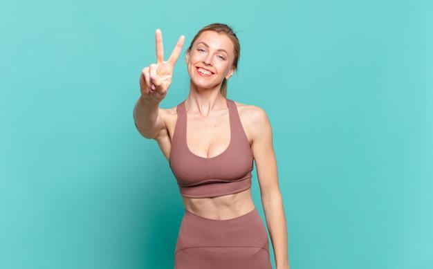 若いブロンドの女性は笑顔で幸せそうに見え、のんきで前向きで、片手で勝利または平和を身振りで示します。スポーツコンセプト