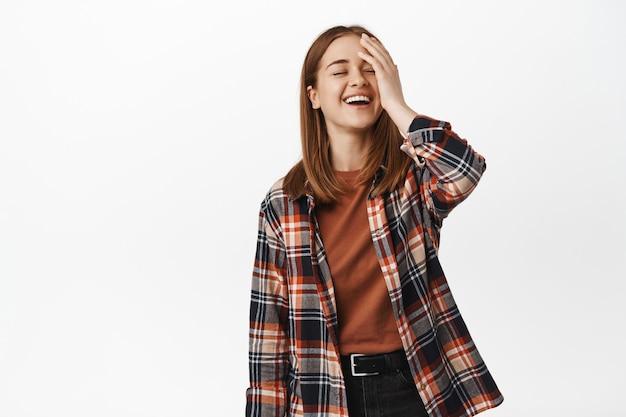 Giovane donna bionda si tocca il viso, ride e sorride, espressione del viso felice, posa spensierata, in piedi in camicia casual a quadri e jeans neri, muro bianco
