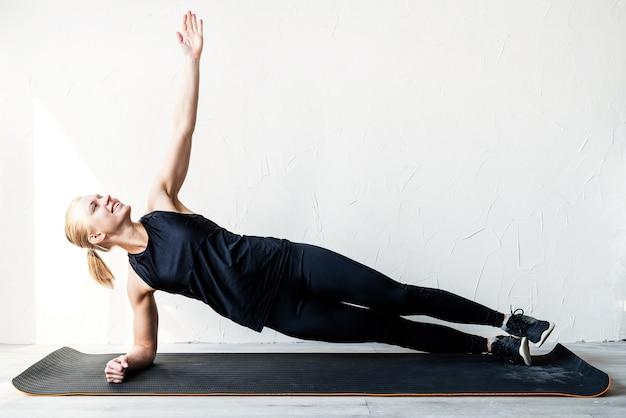 板の位置で自宅でトレーニングしている若いブロンドの女性