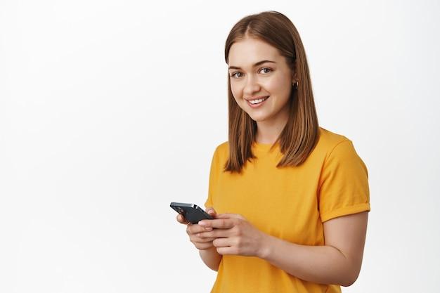 Молодая блондинка женщина с помощью мобильного телефона, текстовое сообщение, улыбается и выглядит счастливым спереди, стоя в желтой футболке у белой стены.