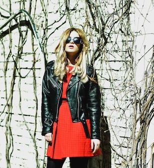 Молодая блондинка женщина в красном платье позирует в городе