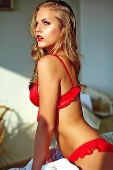 朝はベッドの上に座っている赤いランジェリーを着ている若いブロンドの女性