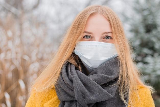 自然の上に白い医療用フェイスマスクを身に着けている若いブロンドの女性