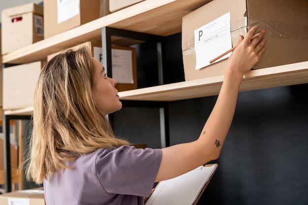 Молодая блондинка со списком заказов и карандашом проверяет адрес получателя на упакованной коробке, стоя у полки в кладовой
