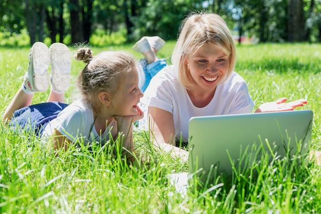 小さな娘と若いブロンドの女性は、ラップトップで公園に横たわり、笑います。夏の晴れた日。愛と優しさ。