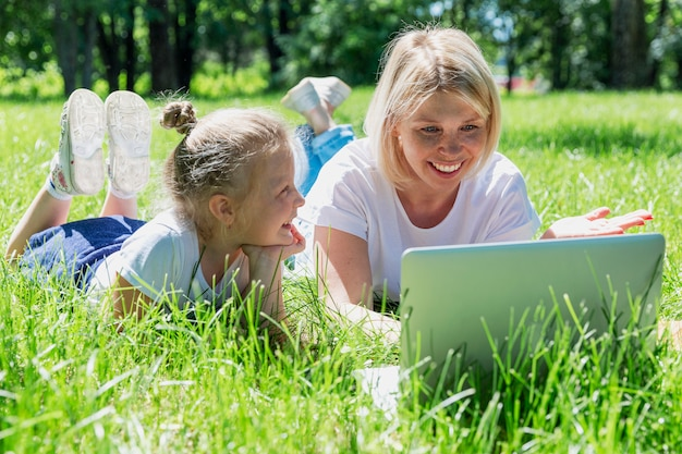 Young blond woman with little daughter lie in the park with a laptop and laugh. summer sunny day. love and tenderness.