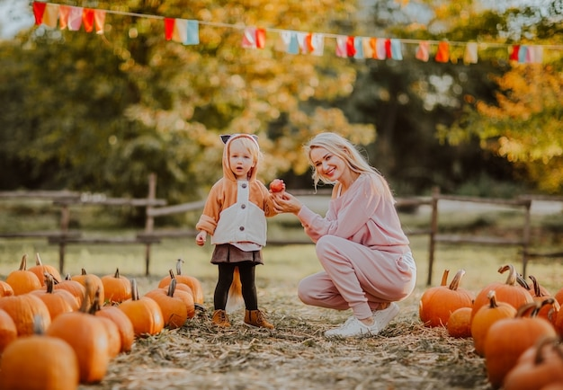 Young blond womant and toddler girl in fox suit posing at the pumpkin's field.autumn time.
