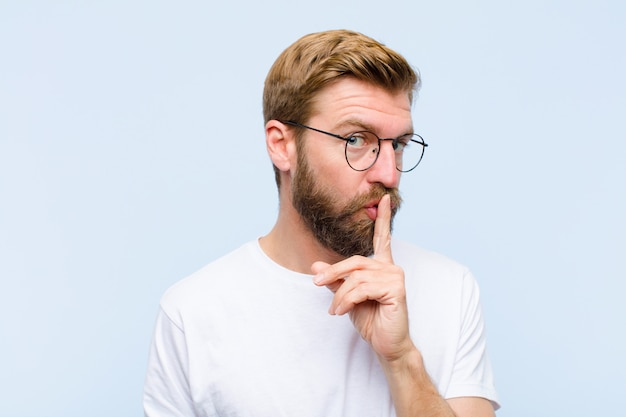 Young blonde adult man asking for silence and quiet, gesturing with finger in front of mouth, saying shh or keeping a secret