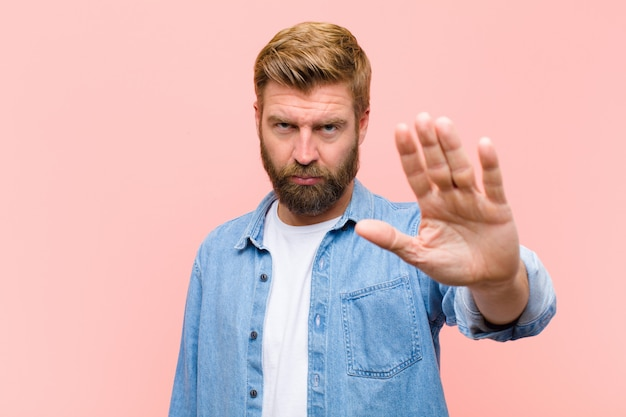 Young blonde adult man looking serious stern displeased and angry showing open palm making stop gesture