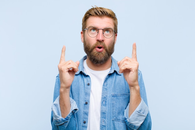Young blonde adult man looking shocked, amazed and open mouthed, pointing upwards with both hands to copyspace