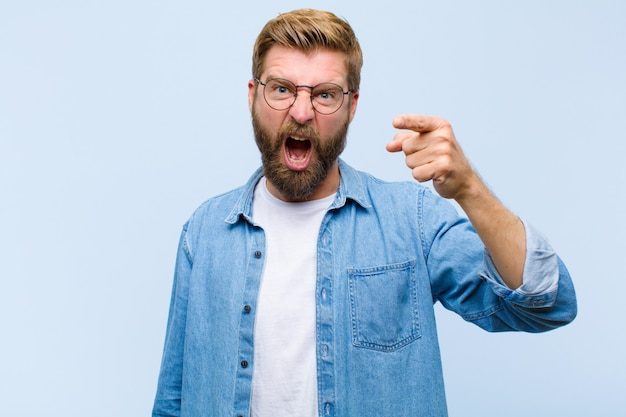 Young blonde adult man pointing at camera with an angry aggressive expression looking like a furious, crazy boss