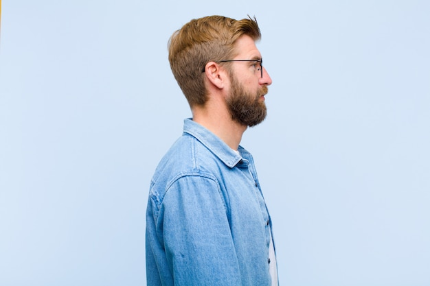 Young blonde adult man on profile view looking to copy space ahead, thinking, imagining or daydreaming