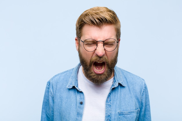 Young blonde adult man shouting aggressively, looking very angry, frustrated, outragedannoyed, screaming no