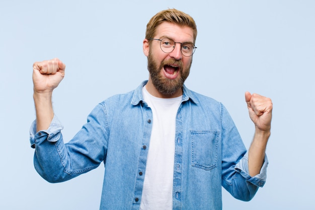 Young blonde adult man shouting triumphantly, looking like excited, happy and surprised winner, celebrating
