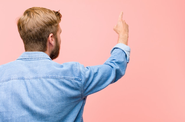 Young blonde adult man standing and pointing to object on copy space, rear view