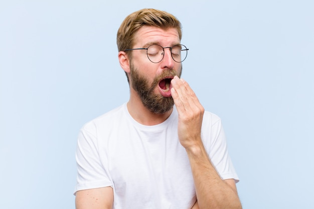 Young blonde adult man yawning lazily early in the morning, waking and looking sleepy, tired and bored