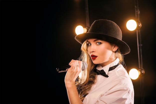 ステージで歌うマイクと白いシャツ蝶の黒い帽子の若い金髪の魅力的な女性