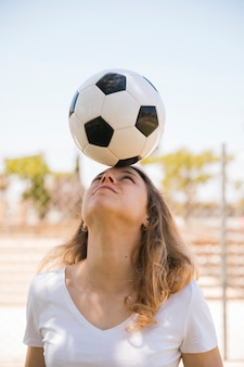 Young blonde balancing soccer ball on head in stadium