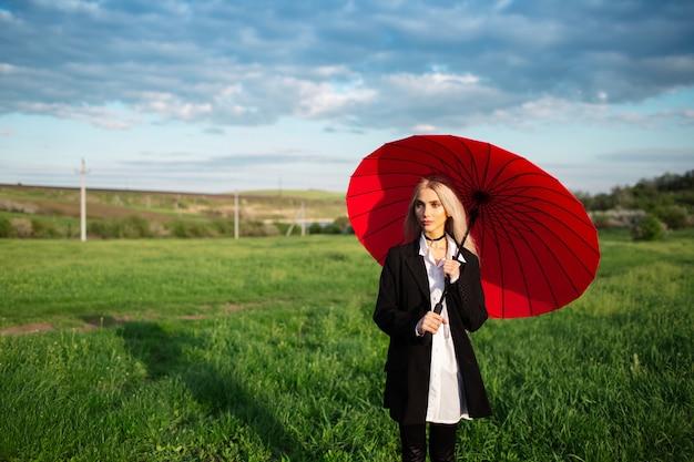 Молодая белокурая красивая девушка, держащая красный зонтик, в черно-белом костюме. предпосылка облачного неба и зеленого поля. женщина в парке на открытом воздухе.