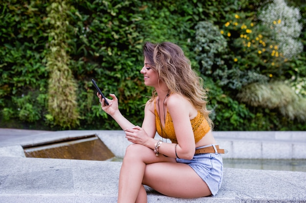 Young blonde beautiful woman at the street using mobile phone and smiling. summertime, green background