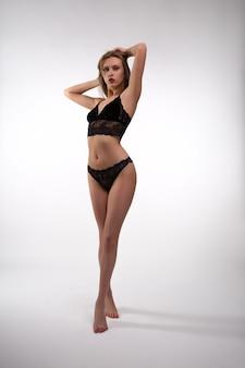 Молодая блондинка-красотка позирует в сексуальном черном кружевном нижнем белье