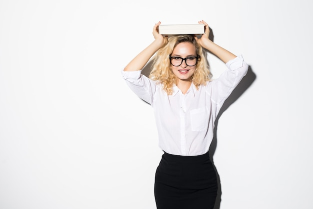 젊은 금발 비즈니스 여자는 머리에 책을 보유하고 흰 벽에 격리됩니다.