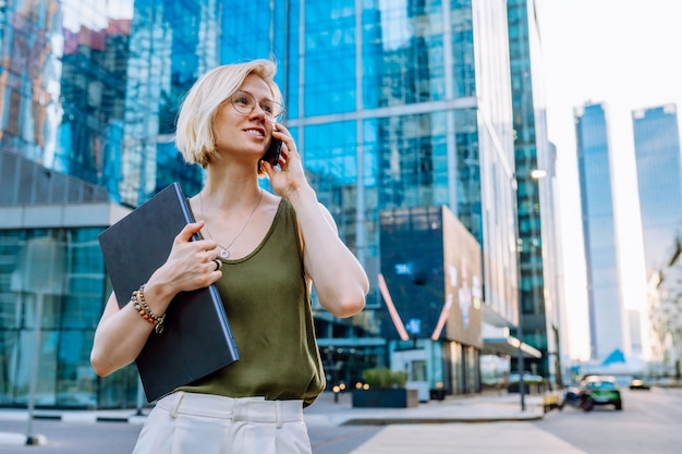 Young blonde business woman standing with laptop among the skyscrapers and speaks on the phone.