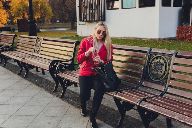 Young blonde business woman with bag in park.