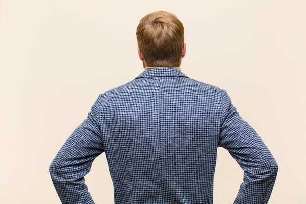 Young blonde businessman feeling confused or full or doubts and questions, wondering, with hands on hips, rear view