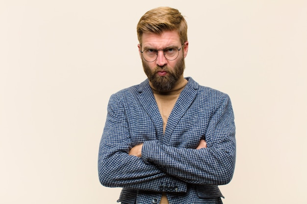 Young blonde businessman feeling displeased and disappointed, looking serious, annoyed and angry with crossed arms
