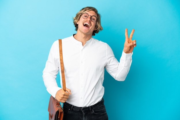 Young blonde businessman isolated on blue smiling and showing victory sign