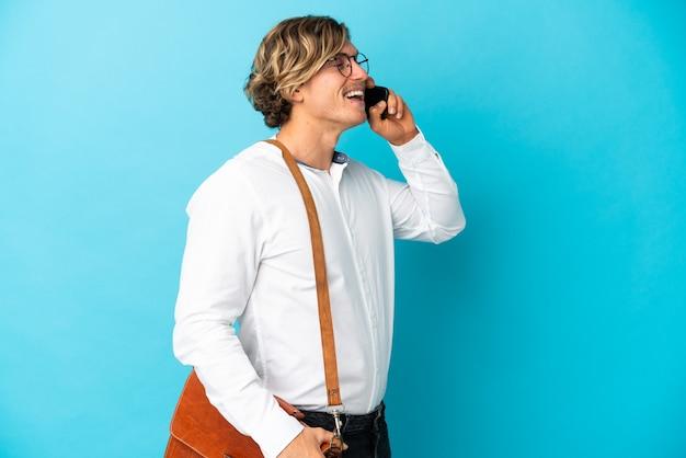 Молодой блондин бизнесмен, изолированные на синем фоне, разговаривая по мобильному телефону