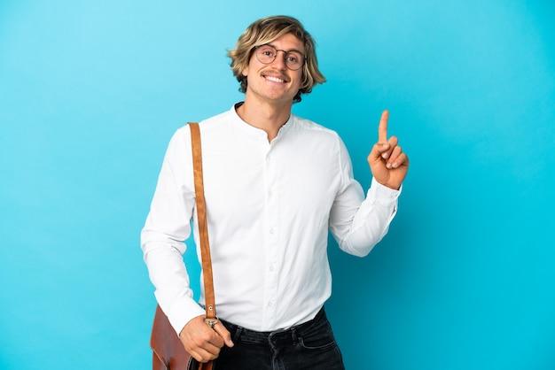 Молодой блондин бизнесмен, изолированные на синем фоне, показывая и поднимая палец в знак лучших