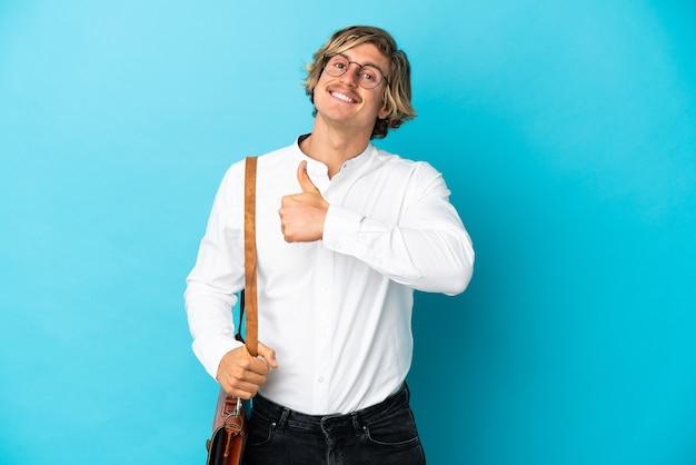 제스처를 엄지 손가락을주는 파란색 벽에 고립 된 젊은 금발 사업가