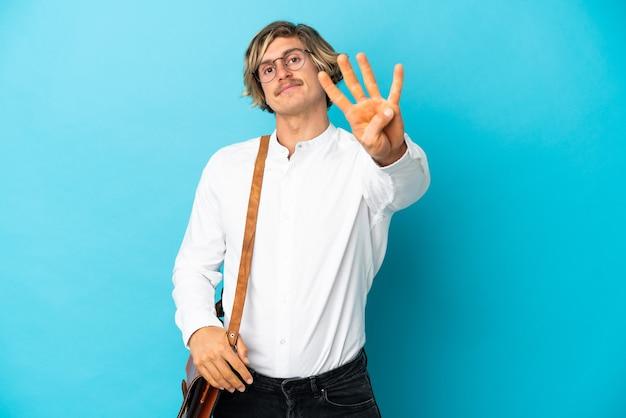 Молодой белокурый бизнесмен изолирован на синей стене счастливым и считает четыре пальцами