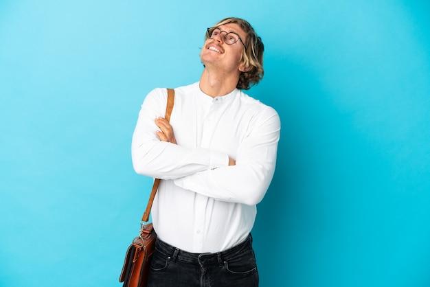 웃는 동안 올려 파란색 벽에 고립 된 젊은 금발 사업가