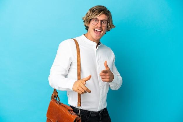파란색 벽 앞에 가리키는 웃 고 고립 된 젊은 금발 사업가