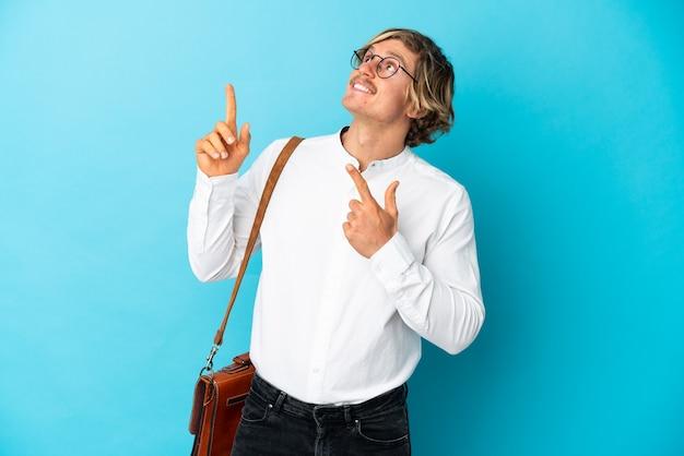검지 손가락으로 좋은 아이디어를 가리키는 파란색 벽에 고립 된 젊은 금발 사업가