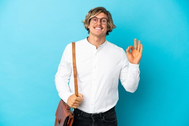 손가락으로 ok 사인을 보여주는 파란색 벽에 고립 된 젊은 금발 사업가