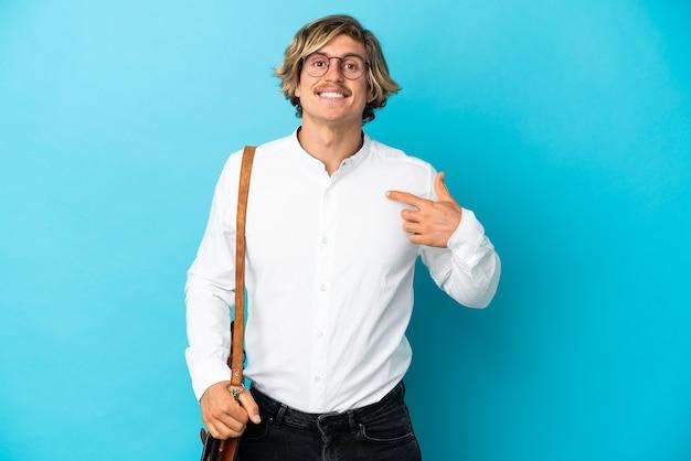 놀라운 표정으로 파란색 벽에 고립 된 젊은 금발 사업가