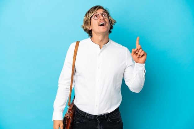 Young blonde businessman isolated pointing up and surprised