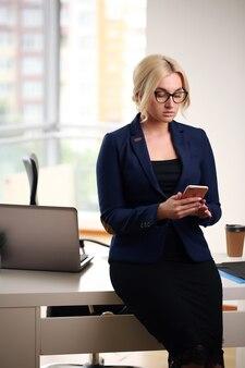 オフィスの机に座っている若い金髪実業家。
