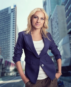 Young blonde businesswoman stands on the street near skyscrapers