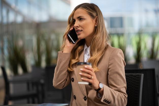 カフェで電話で話している若い金髪の実業家